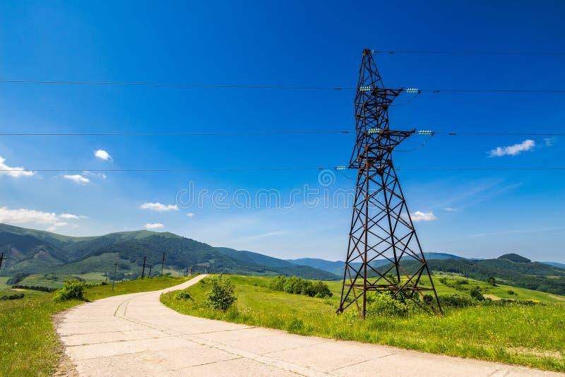 Högt spänningskraftledningtorn i berg royaltyfri fotografi