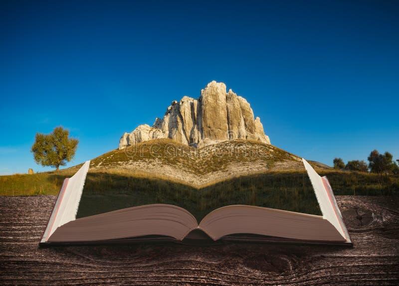Högt stenigt berg på sidorna av en öppen magisk bok fotografering för bildbyråer