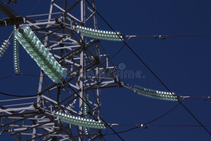 Högt torn för spänningsöverföringsmakt med glass isolatorer blå sky royaltyfri fotografi