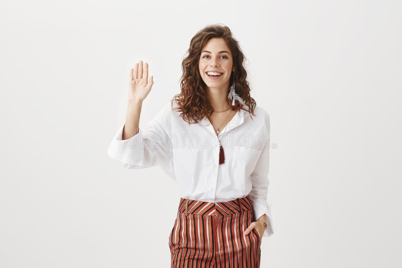 Högt vad är upp Stående av den bekymmerslösa vänliga europeiska kvinnliga entreprenören som rymmer handen i fack och i huvudsak l arkivfoto