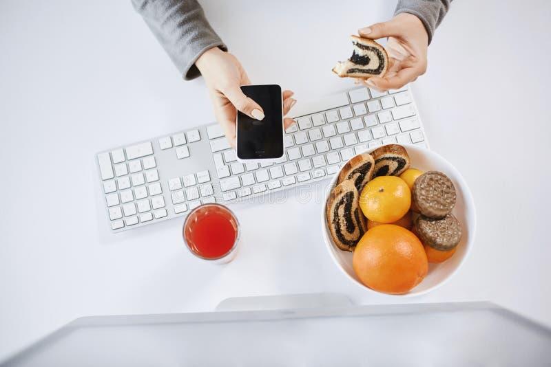 Högt vinkelskott av kvinnan som har lunch framme av datoren och att rymma den rullande kakan och smartphonen Den upptagna kvinnan royaltyfri fotografi