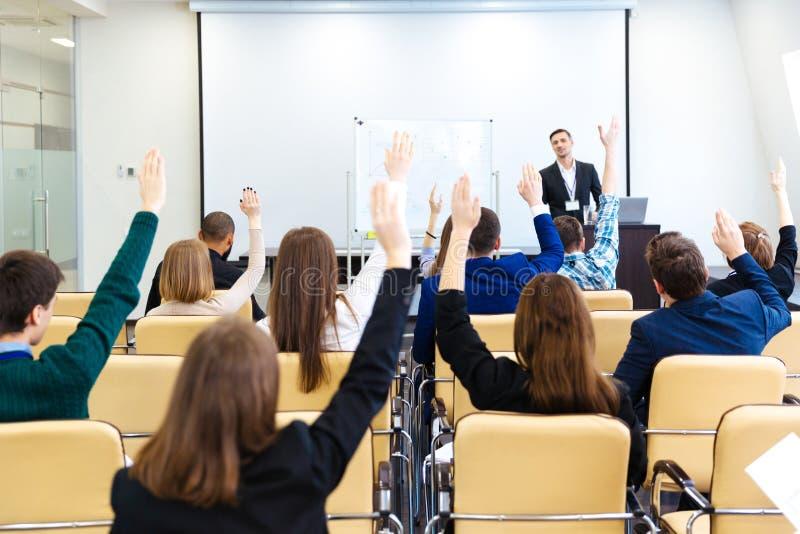 Högtalare som svarar frågorna av åhörare på affärskonferens arkivbild