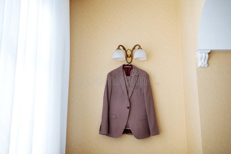Högvärdig dyr dräkt för strikta män som hänger på hängare under lampan arkivbild