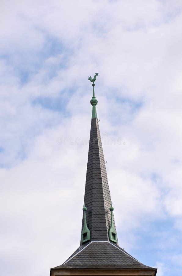 Högväxt belagd med tegel tornspira på ett tak som övervinnas av en hane arkivbild