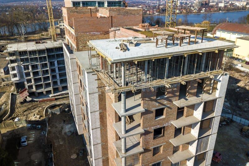 Högväxt byggnad för lägenhet eller för kontor under konstruktion, bästa sikt Tegelstenväggar, material till byggnadsställning och royaltyfri fotografi