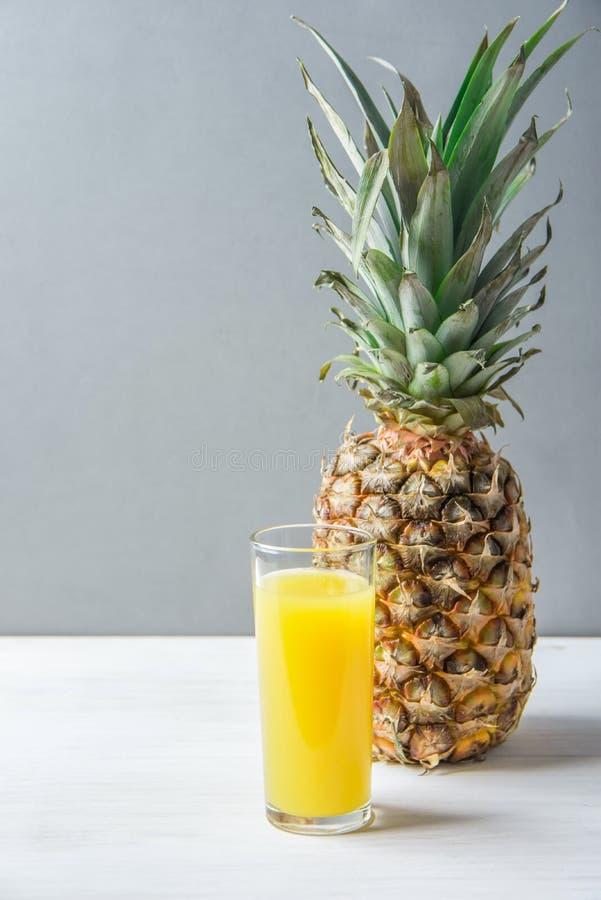 Högväxt exponeringsglas för hel ananas med nytt pressande orange citrus fruktsaft på det vita köksbordet Grey Stone Wall Vitaminm arkivbild