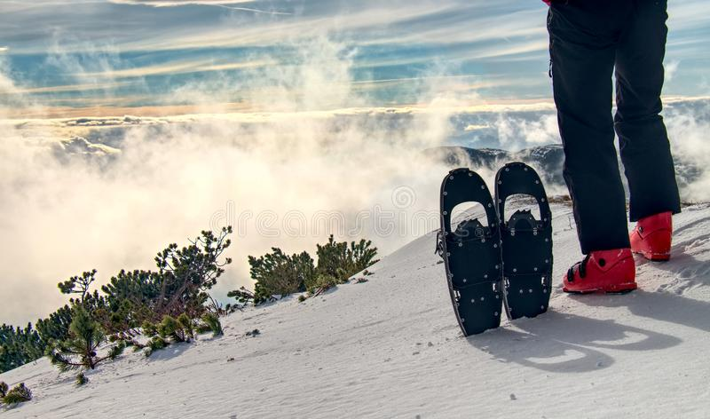 Högväxt idrottsman i varm kläder i snöskor med trekking poler royaltyfria foton