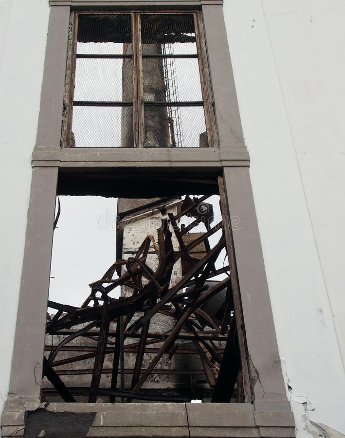 Högväxt industriell lampglas som är synlig till och med ett brutet fönster av en gammal övergiven fabrik med vridna balkar royaltyfria bilder