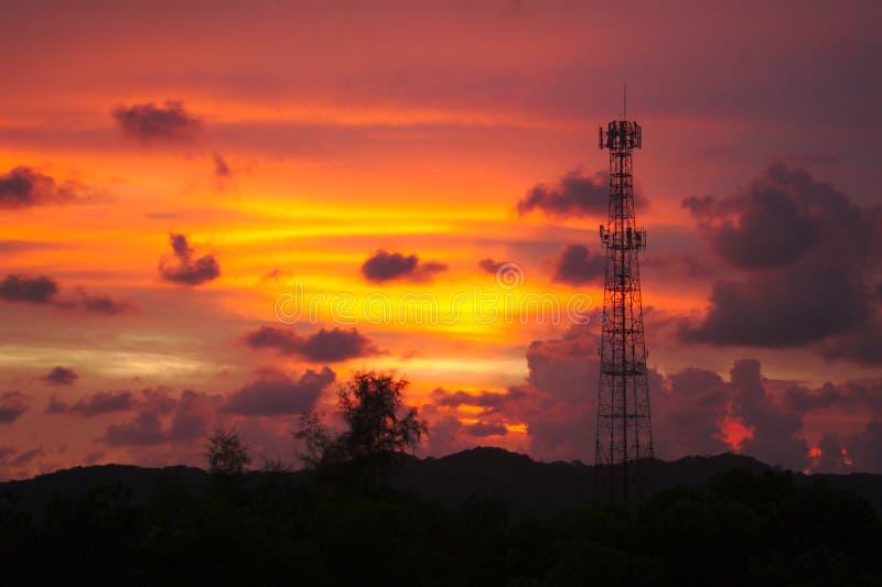 Högväxt mobilt mobiltelefontorn på den höga kullen som överför signalen att förbinda människor världen runt i aftonen då solnedgå royaltyfri foto