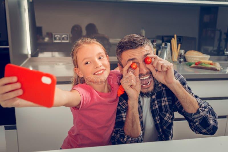 Högväxt skäggig mörker-haired fader och hans nätt dotter som gör selfie royaltyfri fotografi