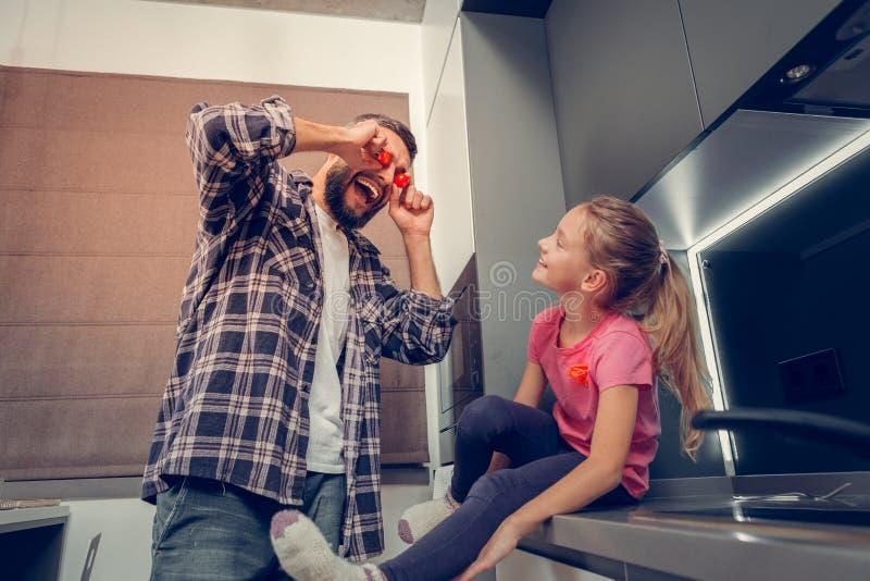Högväxt skäggig mörker-haired fader som skrattar med hans dotter arkivbild