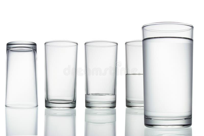 Högväxt töm, halvt och fullt exponeringsglas av vatten på vit med arkivbilder