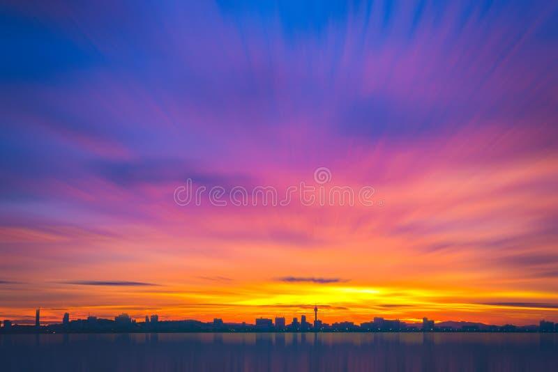 Högväxta byggnader för kontur med härlig himmel och havet på solnedgången K royaltyfria bilder