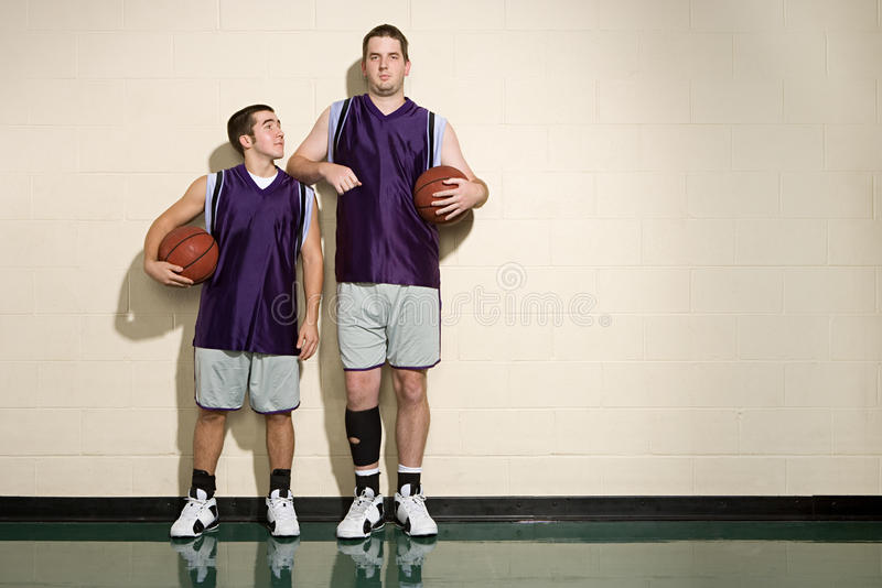 Högväxta och korta basketspelare arkivbilder