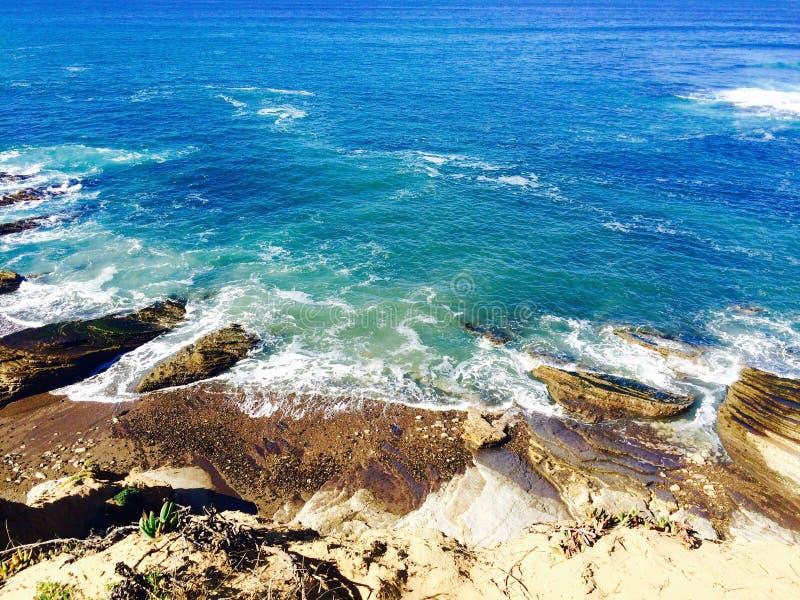Högvatten för blå gräsplan mot en stenig kust royaltyfri foto