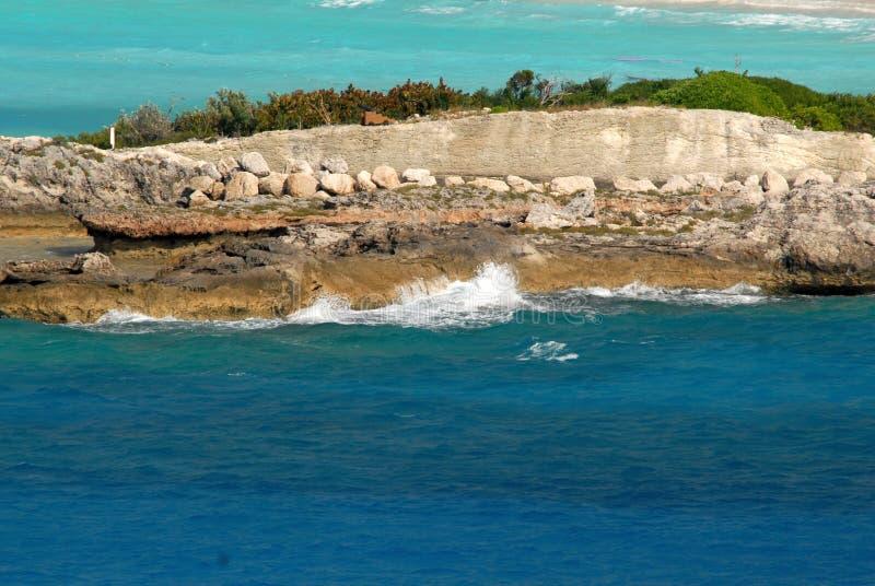 Högvatten vinkar att krascha mot mannen som göras havsväggen av en tropisk ö arkivbild