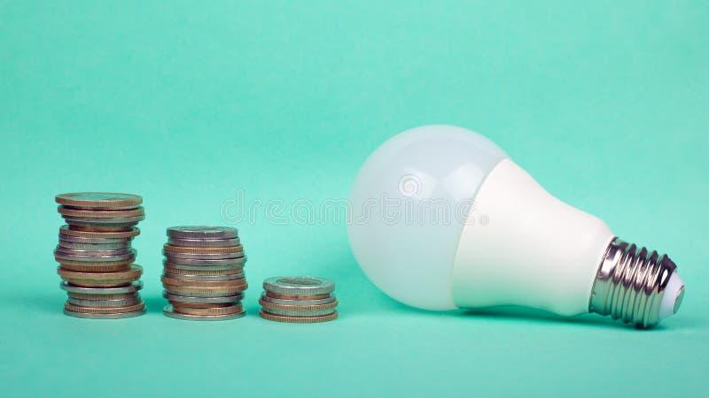 Höhere Stromtarife, wirtschaftliche grüne Elektrizität, LED-Lampen und Münzen lizenzfreies stockfoto