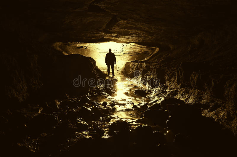 Höhle mit Mannschattenbild und -wasser lizenzfreie stockbilder