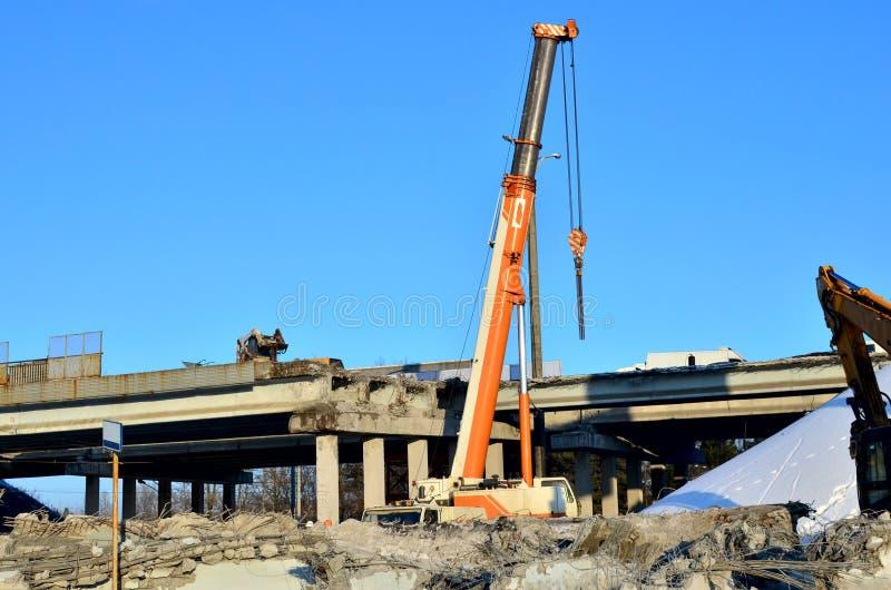 Höja den mobila kranen som demonterar en stor förstärkt konkret tjock skiva, konstruktion av en bilbro på en konstruktion arkivfoto