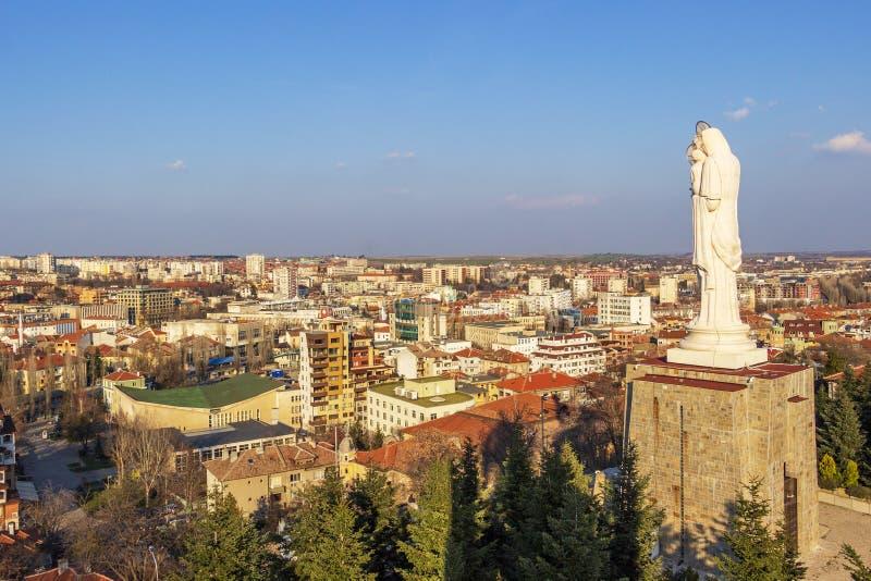 Höjd sikt till staden av Haskovo, Bulgarien och monumentet av den heliga modern av guden, den högsta statyn av oskulden Mary in arkivbilder