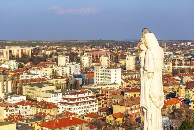 Höjd sikt till staden av Haskovo, Bulgarien och monumentet av den heliga modern av guden, den högsta statyn av oskulden Mary in royaltyfria bilder