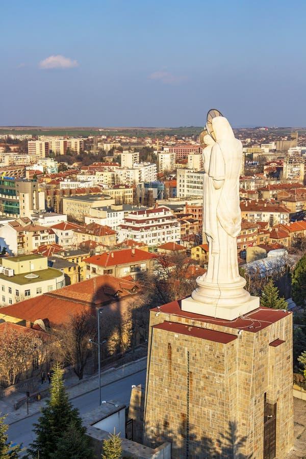 Höjd sikt till staden av Haskovo, Bulgarien och monumentet av den heliga modern av guden, den högsta statyn av oskulden Mary in arkivbild