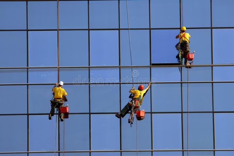 höjdmän som tvättar fönster royaltyfri foto