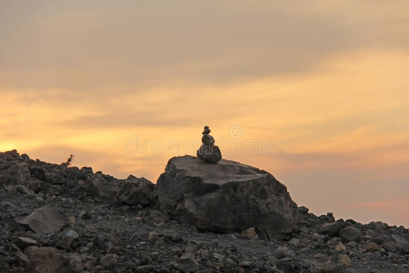 Höjdpunkt eller pyramid av stenar på Volcano Peak, på solnedgången, på den Vulcano ön, Italien royaltyfria bilder