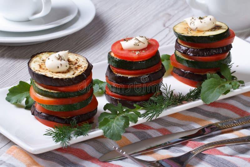 Höjdpunkter av den bakade tomaten, zucchini, aubergine på en vit platta arkivfoton