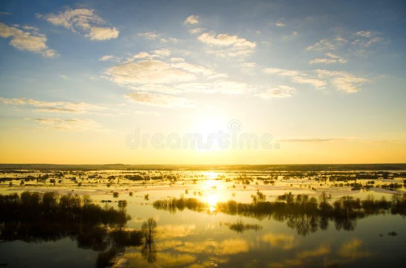 Höjdvattenflod på solnedgång. royaltyfri fotografi