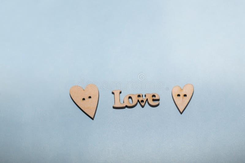 Hölzerne Aufschrift 'Liebe 'und zwei Herzen - Knöpfe auf einem blauen Hintergrund stockfoto