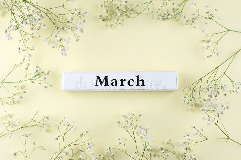 Hölzerne Aufschrift des Frühlingsmonats März auf einem gelben Hintergrund lizenzfreies stockfoto