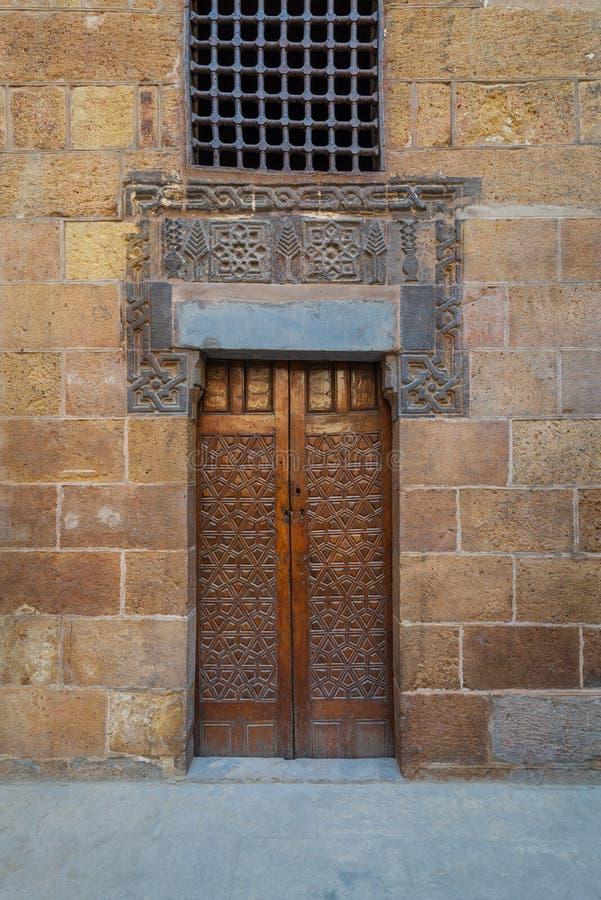 Hölzerne aufwändige Tür mit geometrischen gravierten Mustern auf externer alter verzierter Ziegelsteinsteinwand, Kairo, Ägypten stockfotos