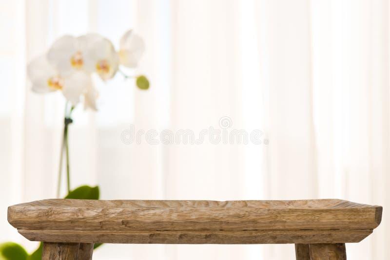 Hölzerne Badezimmertabelle auf Zusammenfassung verwischte Hintergrund mit Orchideenblume lizenzfreie stockfotografie