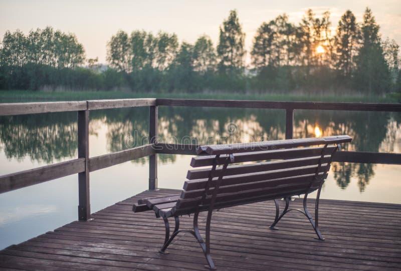 Hölzerne Bank und Sonnenuntergang nahe einem See lizenzfreies stockfoto