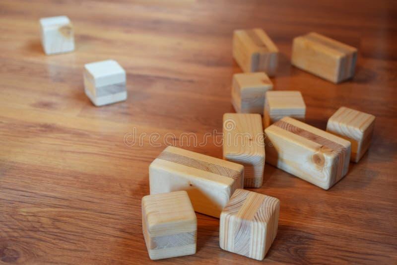 Hölzerne Bauklötze und Würfel auf braunem Boden lizenzfreie stockfotos