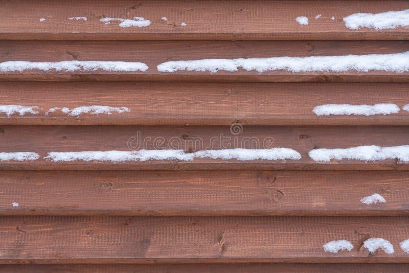 Hölzerne Beschaffenheit Hintergrundbraunholzverkleidungen bedeckt mit Schnee stockfotos