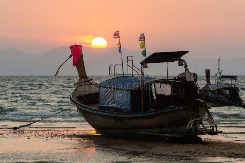 Hölzerne Boote des langen Schwanzes festgemacht an Strand Klong Muang bei Sonnenuntergang in Krabi-Provinz, Thailand lizenzfreie stockbilder