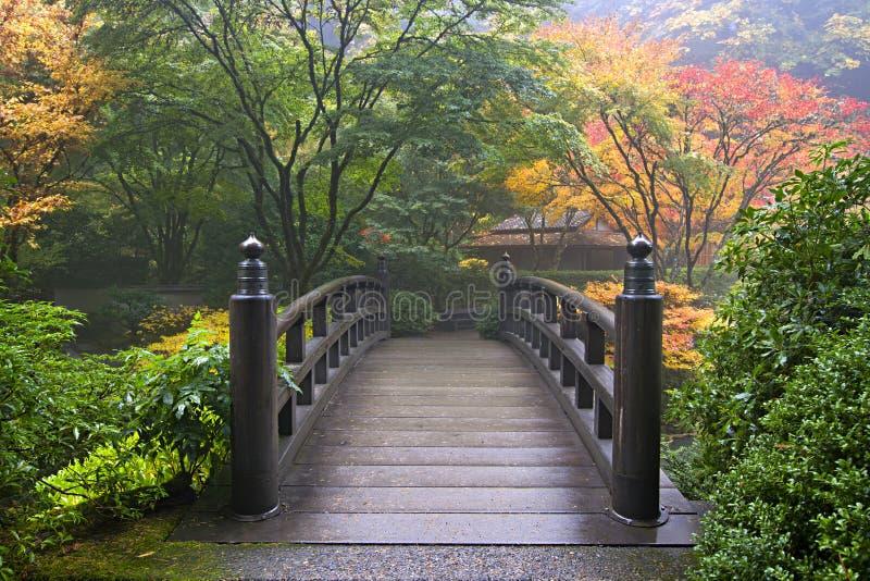 Hölzerne Brücke am japanischen Garten im Fall lizenzfreies stockbild