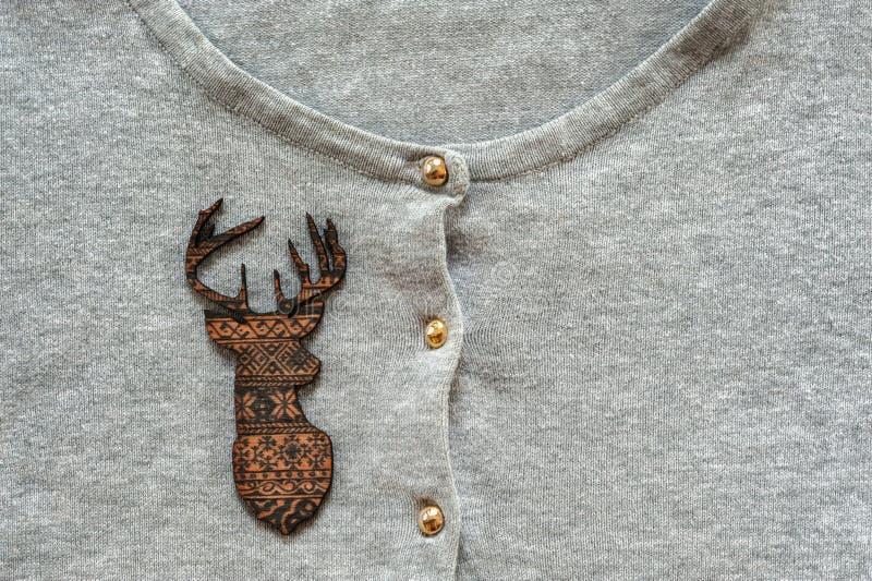 Hölzerne braune Rotwild auf grauem Pullover lizenzfreie stockbilder