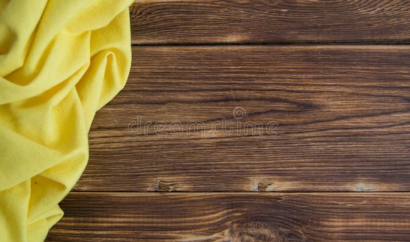 Hölzerne braune Tabelle mit tadellosem Serviettengelb lizenzfreies stockfoto
