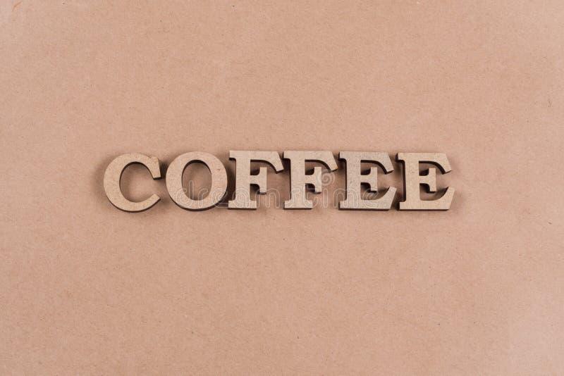 Hölzerne Buchstaben der Wortkaffee-Zusammenfassung Altes Kraftpapier des Hintergrundes, Kopienraum lizenzfreies stockfoto