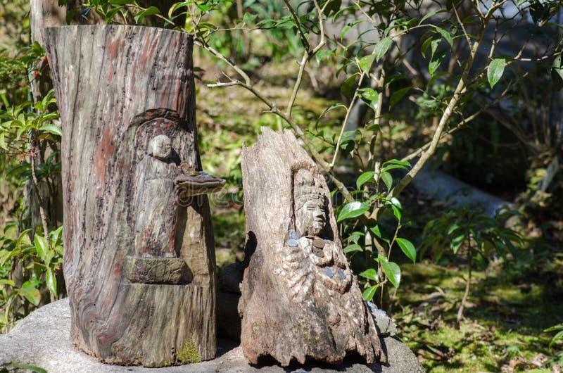 H?lzerne Buddha-Skulptur mit gespendeten M?nzen in Kamakura stockfotografie