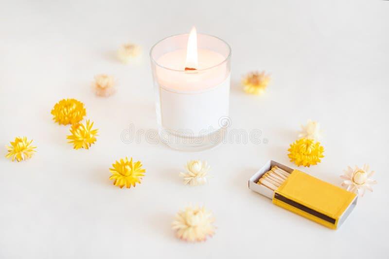 Hölzerne Dochtkerze mit Match und gelben Blumen Elegante Inneneinrichtung Brennende duftende Kerze des Wachses lizenzfreie stockbilder