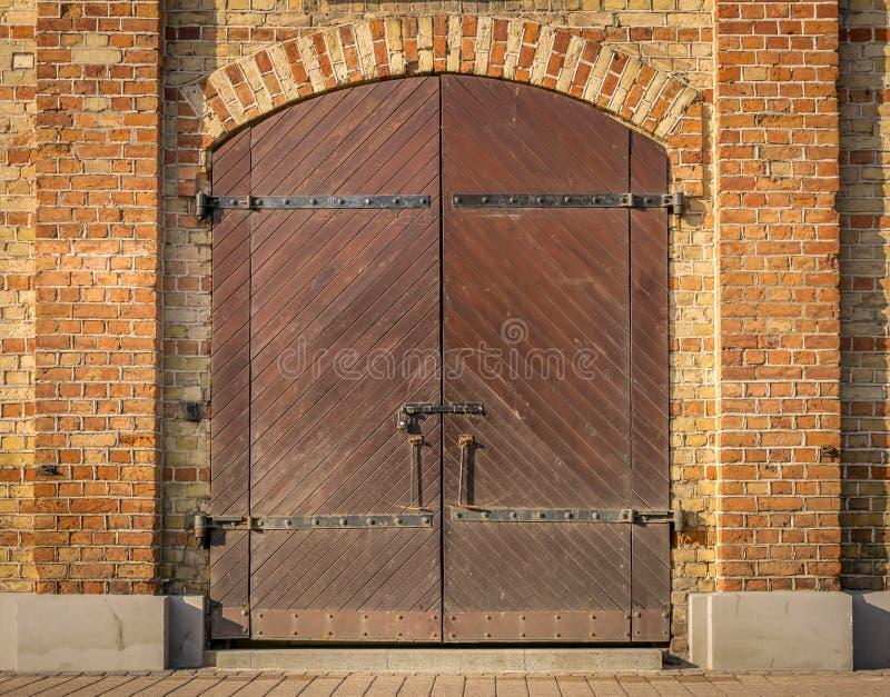 Hölzerne Doppeltüren Browns mit einem Bogen des roten Backsteins stockbild