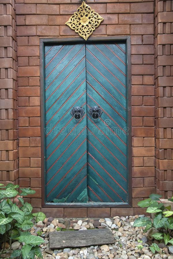 Hölzerne Doppeltüren des Weinlesegrüns der braunen Backsteinmauer lizenzfreie stockfotografie