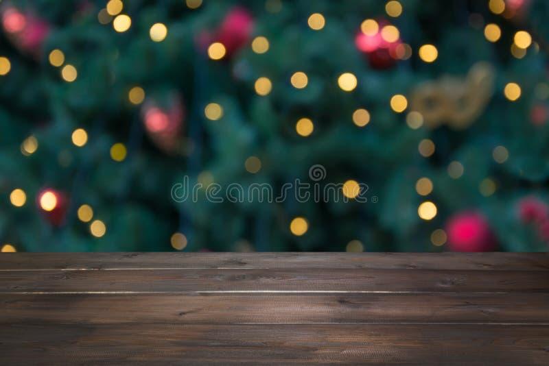 Hölzerne dunkle Tischplatte und unscharfes Weihnachtsbaum bokeh Weihnachtshintergrund für Anzeige Ihre Produkte stockbilder