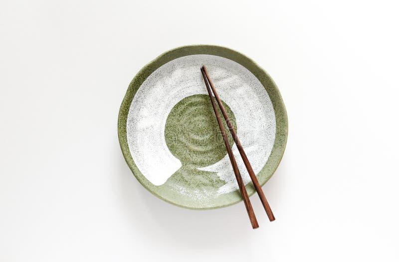 Hölzerne Essstäbchen auf keramischer Platte stockfoto