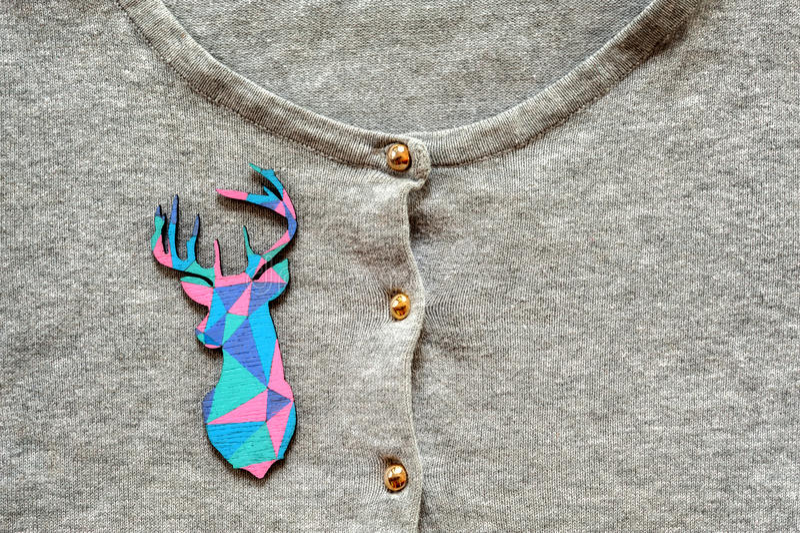 Hölzerne farbige Rotwild auf grauem Pullover lizenzfreie stockbilder