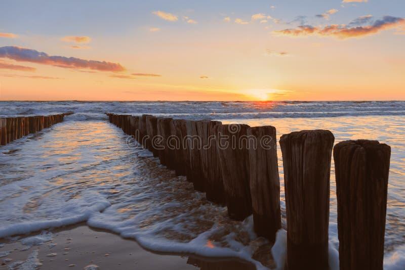 Hölzerne Fenne, die in das Meer mit Sonnenuntergang laufen stockfotografie